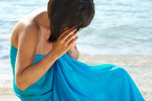Young woman crying on the beach