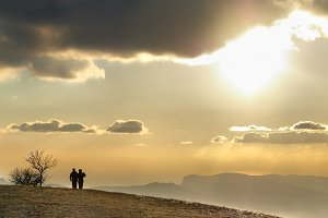 Couple on the hill at sunset