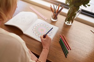 Woman drawing in colouring book