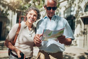 Mature man and woman using map
