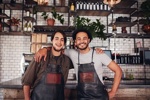 Happy young male bartenders