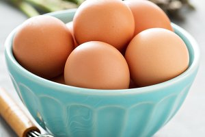 Fresh eggs in a bowl with whisk