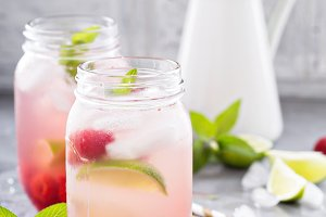 Cold green iced tea with lime and raspberry