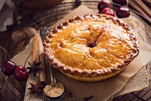 Cherry pie on rustic background