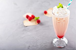 Iced milkshake with raspberry syrup and whipped cream