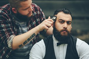 barber shaves a bearded man