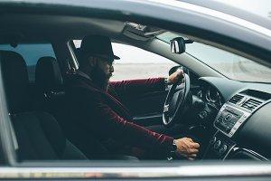 Man with beard driving a car