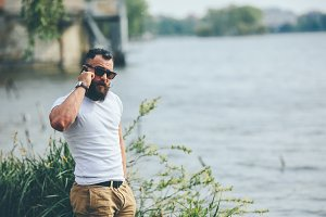 American Bearded Man using phone near the river