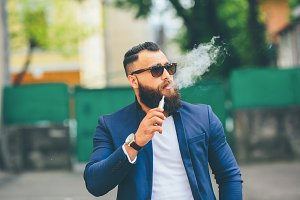 well-dressed man smoking electronic cigarette