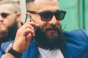 Two bearded businessman looking at phone