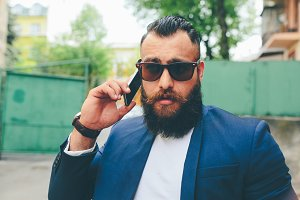 Bearded businessman looking at phone