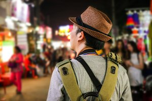 Young male backpacker walking in a famous street night market in Asia