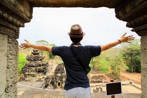 Young man spreading his hands in Angkor temples in Siem Reap, Cambodia.
