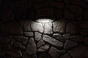 Lamp casting light on stone wall