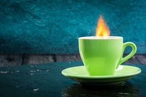 A cup of coffee with a flame