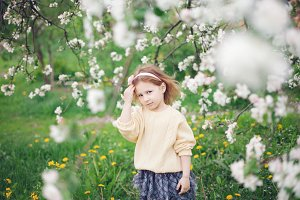 Little girl near the blooming tree