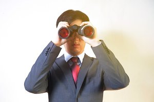 Asian Businessman looking for something with binoculars such as business opportunities / jobs / new market - business issues discovery concept