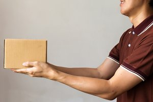 Delivery man giving a cardboard box on white background with copy space