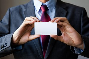 Young man in business suit holding white blank business card. Business name card presenting (mock up white card)