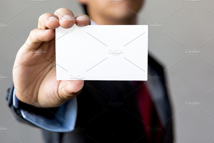 Young man in business suit holding white blank business card ...