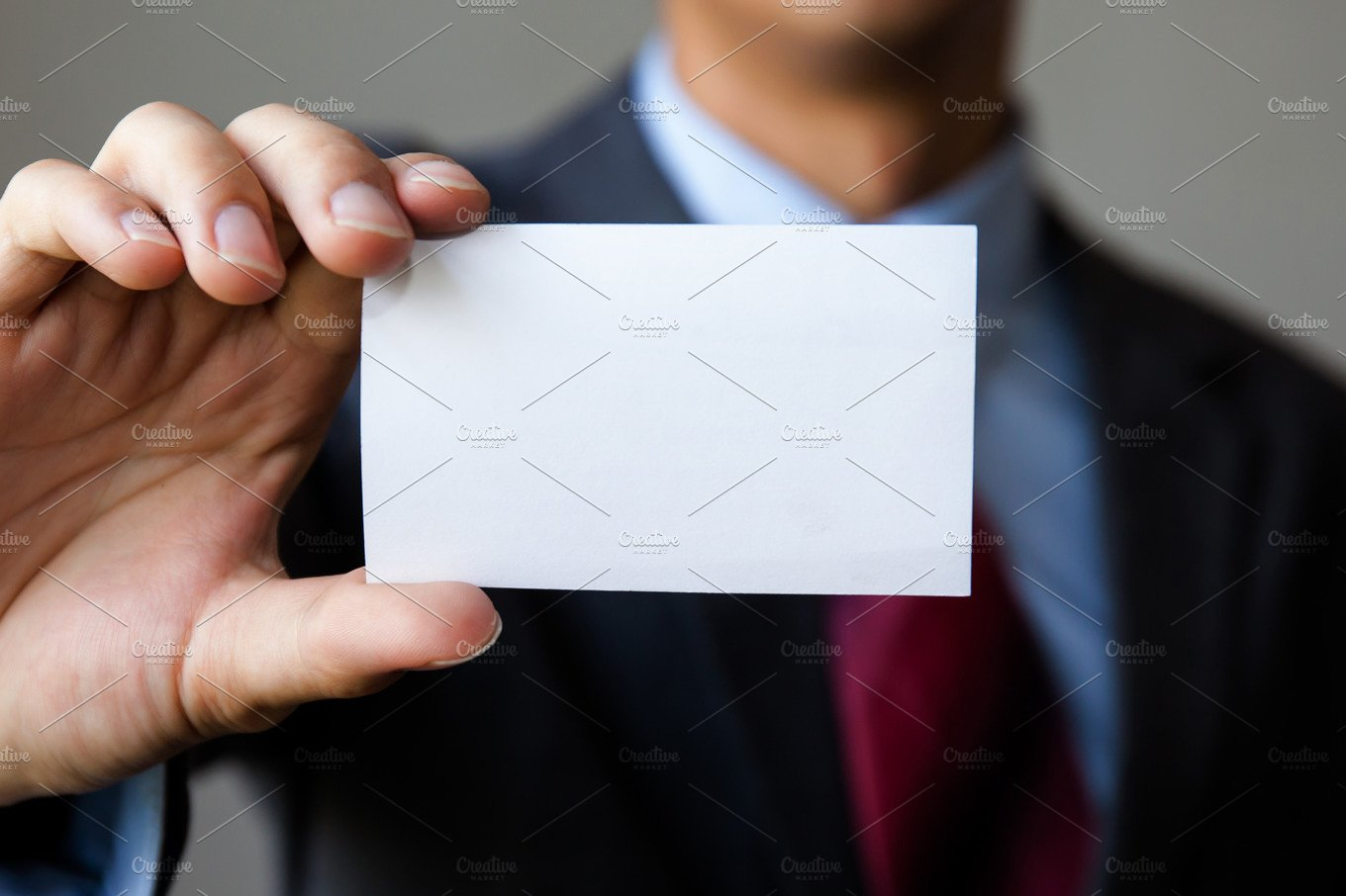 young man in business suit holding white blank business card business name card presenting mock up white card people images creative market - Blank Business Cards