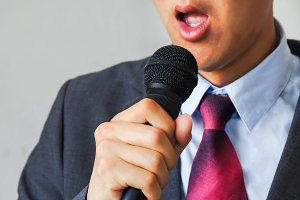 Young talking man holding microphone without confidence on isolated white background