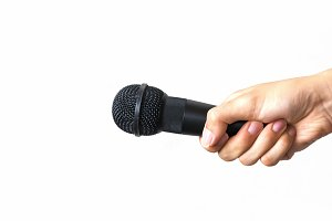 Male hand with microphone on isolated white background. Business and public speech concept