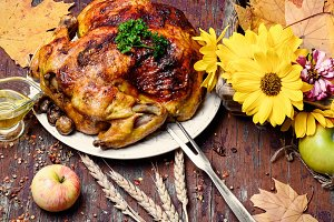 Roasted chicken on wooden plate