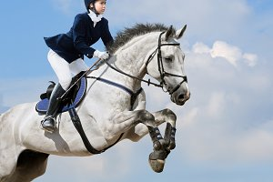 Woman jumping with grey horse