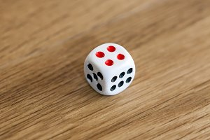 Photo of white dice being rolled on wooden background