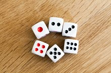 Photo of six white dices being rolled on wooden background