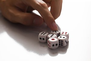Human hand ready to roll the dice in very dark tone against the light - Try luck, Take Risk or Business concept (Focus on dices)