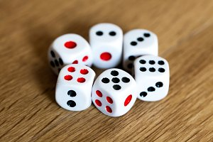 Photo of four white dices being stacked up on wooden background