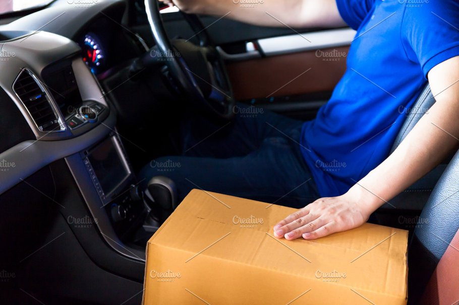 Delivery Man Driving A Truck With Cardboard Package On The Front Seat