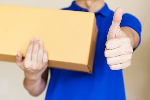Delivery man giving thumbs up as he carries a package isolated on white background (Focus on Hands)
