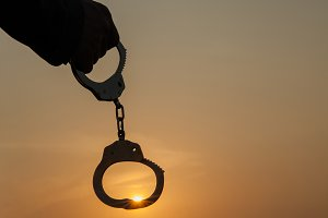 Business Man holding handcuffs after releasing over sunset background. Freedom and Burden-free concept