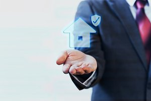 Businessman presenting virtual house with protection on his palm of hand - house insurance concept