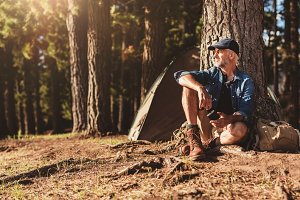 Mature man sitting at a campsite