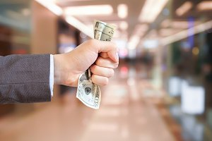 Businessman grasping and giving money in shopping mall blurred background