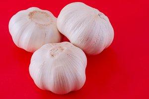 Three garlics on red background