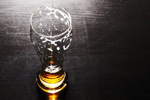 drained glass of lager beer on table