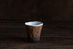 brown and white clay cup