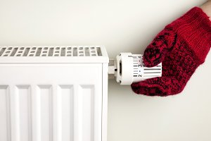 Hand holding radiator thermostat