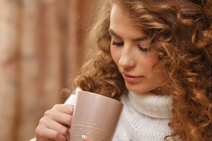 Woman drinking a hot drink.