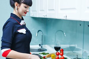 Girl cooks tomatoes for dinner.