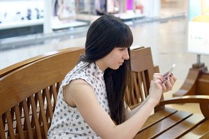 Young woman playing Pokemon GO indoor at shopping center, using smart phone. Girl sit at bench play the popular smartphone game - catching pokemon in hypermarket mall