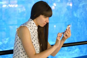 Young woman playing Pokemon GO indoor at oceanarium, using smart phone. Girl play the popular smartphone game - catching pokemon