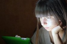 Young woman with tablet computer lying on sofa. Girl using tablet computer at home late night. Glowing light on face. She uses mobile device to shopping online, reading social media, surf the internet