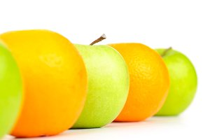 apples and oranges in row isolated on white
