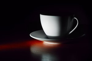 white cup on saucer in dark